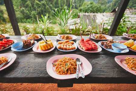 Lunch in the middle of the jungle. The table full of foods and fruits. Traditioal Pad Thai, spring rolls, melon and pineapple. Chiang Mai Province, Thailand. Archivio Fotografico