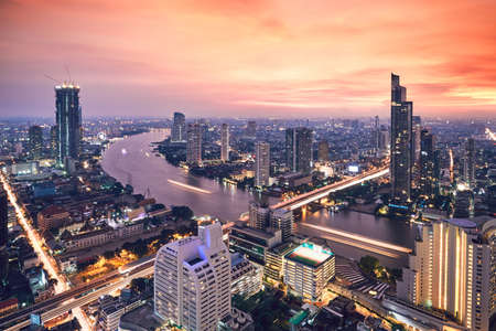 Bangkok during golden sunset. City skyline with traffic on the roads and Chao Phraya River.  에디토리얼