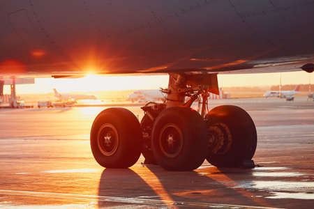 Landing gear of the airplane. Amazing sunset at the airport. Standard-Bild