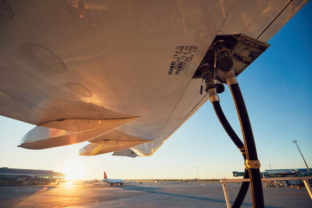 Amazing sunset at the airport. Refueling of the airplane before flight.  Stock Photo