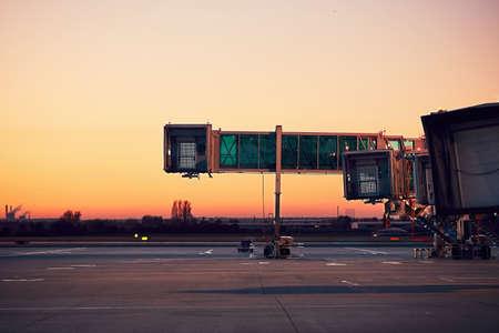 空の搭乗橋。カラフルな夕日の空港。