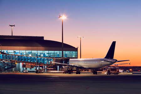 飛行前に飛行機の準備。カラフルな夕日の空港。