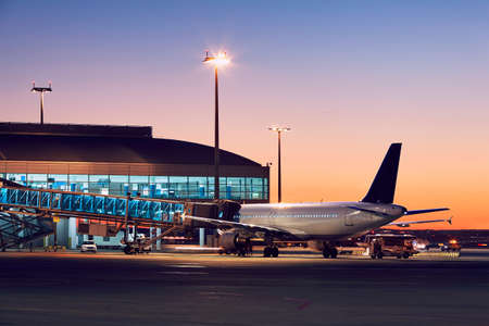 Preparation of the airplane before flight. Airport at the colorful sunset. Standard-Bild
