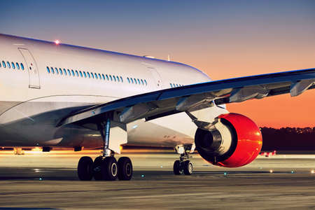Airplane on the runway. Airport at the amazing sunset.