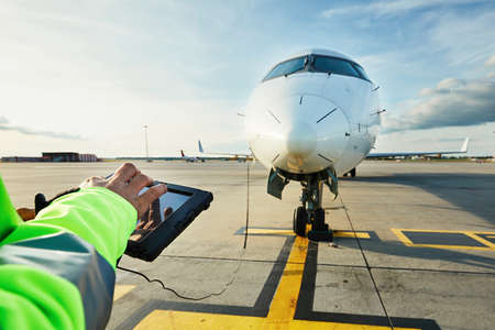 Modern technology at the airport. Member of the ground staff preparing the passenger airplane before flight. Banco de Imagens
