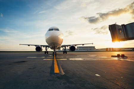 놀라운 일몰에 공항. 비행기가 문을 향해 택시를 타고 있습니다. 스톡 콘텐츠