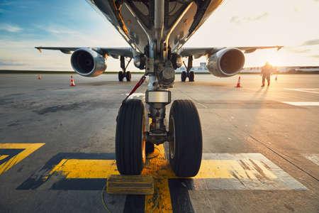 素晴らしい夕日の空港。対向する空港での飛行機の低角ビュー。飛行前に旅客機を準備する地上スタッフのメンバー。- 車輪に焦点を合わせる。