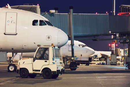 Busy airport at night. Preparation of the airplanes before flight.