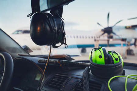 View from car of the ground staff at the airport. Selective focus on the reflective green headphones. Standard-Bild