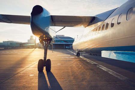 日の出の空港。飛行前のプロペラ飛行機。