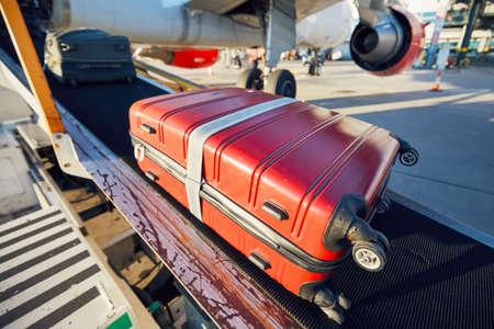 空港で忙しい一日。手荷物の積み込みとフライト前の飛行機の準備。- 選択的フォーカス