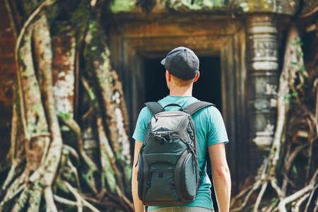 カンボジアのシェムリアップ(アンコールワット)近くの木の巨大な根の下に古代のモニュメントに来るバックパックを持つ若者 写真素材