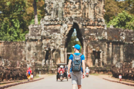 Traveler in the ancient city. Young man with backpack coming to ancient monuments. Siem Reap, Cambodia