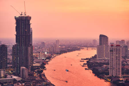 Bangkok during amazing sunset. City skyline with traffic on the roads and Chao Phraya River. Standard-Bild
