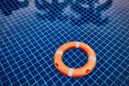 Orange lifebuoy floating on the water surface of the swimming pool against reflection of the palm trees. Zdjęcie Seryjne