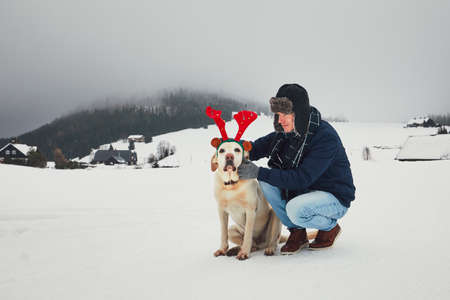 Funny walk with dog in the snowy landscape. Labrador retriever is wearing fake reindeer antlers. Winter season in Jizera Mountains, Czech Republic.