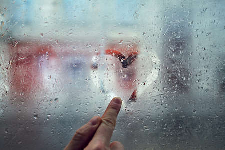 Finger of the young man drawing heart shape on the window with raindrops against city street.