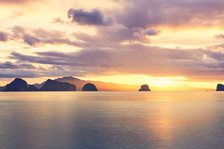 Amazing sunrise on the sea. Silhouettes tropical islands between Phuket and Krabi in Thailand.