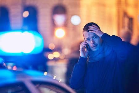Giovane che chiama dopo una situazione di crisi sulla via della città. Temi criminalità, servizio medico di emergenza, paura o aiuto. Archivio Fotografico - 92672999