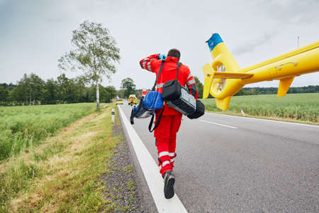 Lekarz z defibrylatorem i innym sprzętem biegnącym z helikoptera. Zespoły pogotowia ratunkowego reagują na wypadek drogowy.