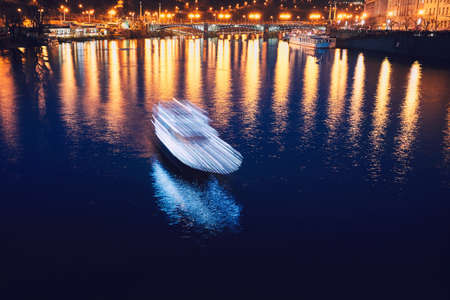 Night cruise through the historic center of the city. Blurred motion of the boat in Prague, Czech Republic.