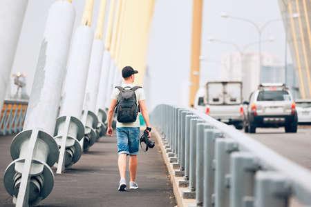 Junger Fotograf (Reisender) mit der Fotokamera, die auf die Brücke geht und nach Inspiration sucht. Bangkok, Thailand