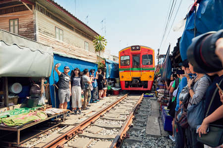 Maeklong, Thailand - November 4, 2017: Railway market on November 20, 2017 near Maeklong station. Train passing through local market is popular tourist attraction close to Bangkok in Thailand. Editorial