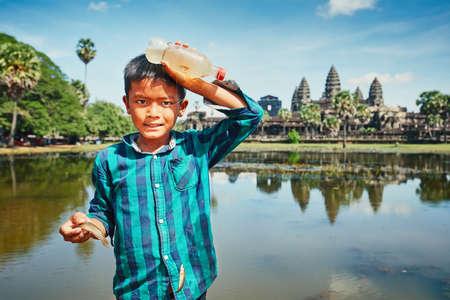 シェムリアップ、カンボジア - 11月10、2017:カンボジアで有名なアンコールワット寺院の前で湖で釣り少年。