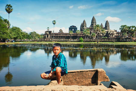 Siem Reap, Cambodia - November 10, 2017: Little boy fishing in lake in front of the famous Angkor Wat temple on November 10, 2017 in Cambodia.