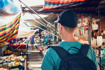 Young man (tourist) walking to open market along the railroad track. Maeklong railway market close to Bangkok in Thailand. Foto de archivo