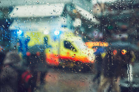 Emergency medical service response in the city. Ambulance cars on the rush street during rain. View through a car window and selective focus on the raindrop. Prague, Czech Republic. Stock Photo