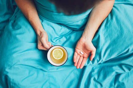 Influenza season. Hand of the sick man holding pill and cup of the hot tea in the bed. Stock Photo