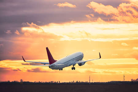 Airplane taking off from the airport runway at the sunset. Imagens