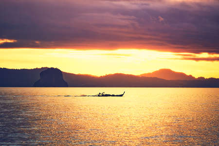 Amazing sunrise on the sea. Silhouette of a small fishing boat against tropical islands between Phuket and Krabi in Thailand