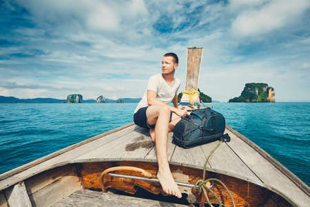 Young man (tourist) with backpack on the traditional long tail boat against islands between Phuket and Krabi in Thailand. Stock Photo