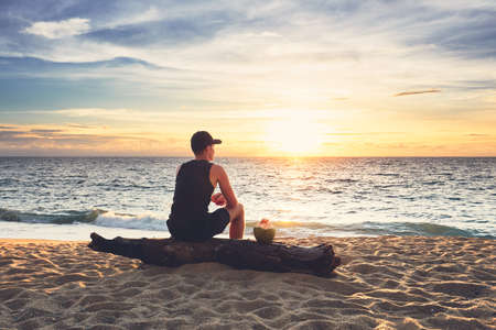 Pensive young man with coconut drink relaxing on the beach during beautiful sunset. Phuket, Thailand.