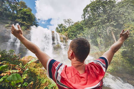 Happy young man (traveler) standing near Wachirathan waterfall in tropical rainforest. Chiang Mai Province, Thailand