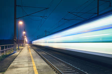 Light trail of the express train in the railway station at the night.