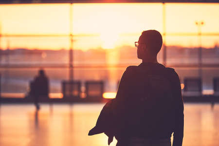 Silhouette of the young man at the airport. Traveler leaves to the gate during golden sunset.  Banque d'images