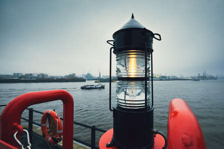 Beacon against freight ship and harbor. Gloomy and cold day in Hamburg, Germany  Stock Photo