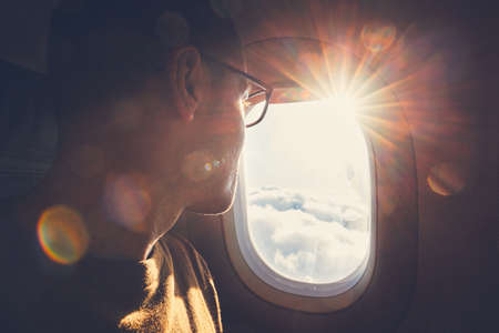 Young man looking out through window of the airplane during beautiful sunrise. Stok Fotoğraf - 95299208