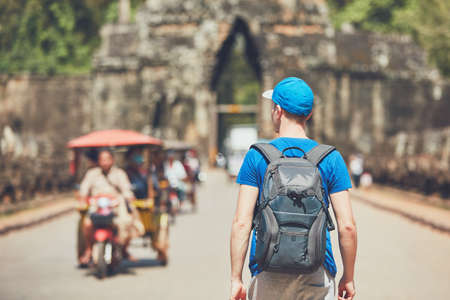 Tourist in the ancient city. Young man with backpack coming to ancient monuments. Siem Reap, Cambodia