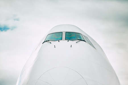 Front view of the airplane nose against cloud sky. Banco de Imagens - 95549304