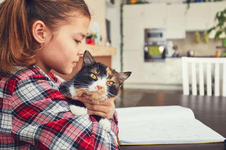Learning at home. Little girl holding tabby cat and doing homework for elementary school.