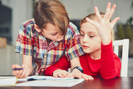 Learning at home. Brother and sister doing difficult homework. Stock Photo