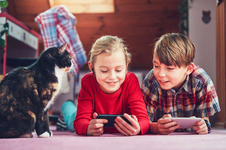 Little girl and boy watching video or playing games on their smart phones.  Stock Photo