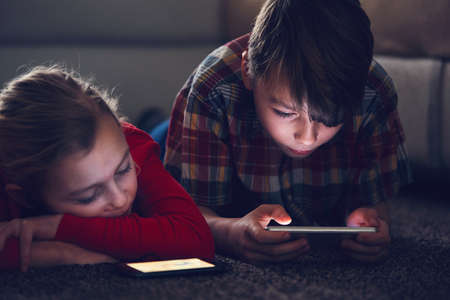 Little girl and boy watching video or playing games on their smart phones.  Imagens