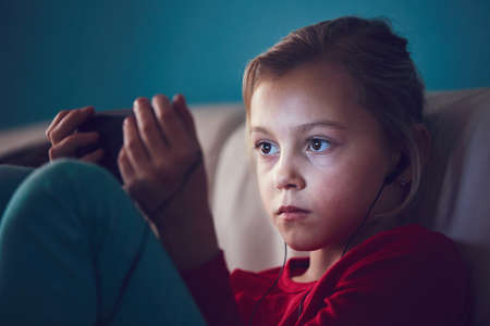 Little girl watching video or playing games on their smart phones. Stock Photo - 95968762