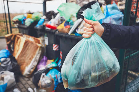 ゴミ袋が歩道にあふれているゴミ箱にゴミを持って手をつなぐ。