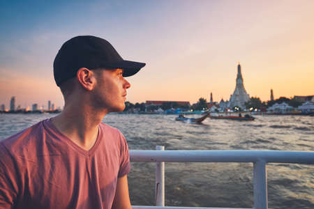 Young man with cap on the boat against temple Wat Arun at the sunset. Chao Phraya River in Bangkok, Thailand.